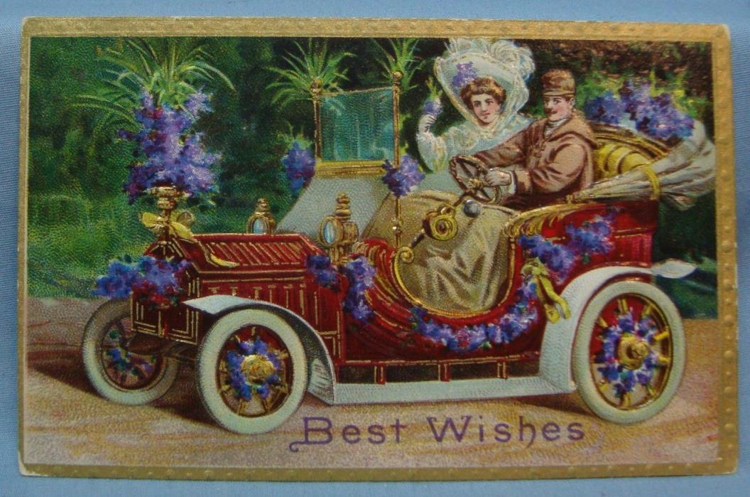 1910 EMBOSSED BEST WISHES MAN WOMAN IN CAR VINTAGE POSTCARD 3G