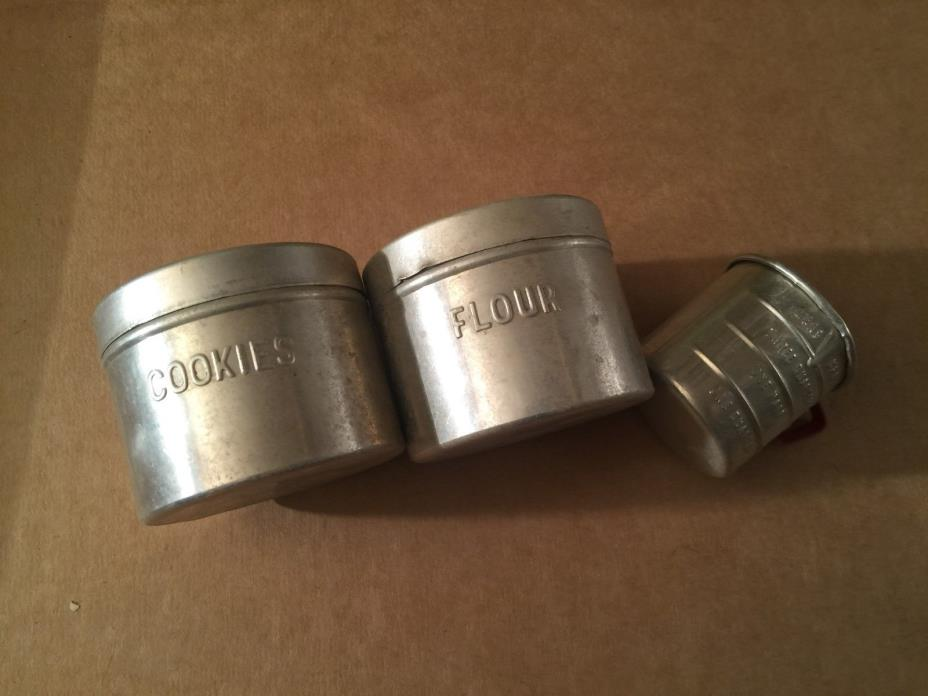Vintage metal canisters and measureing cup
