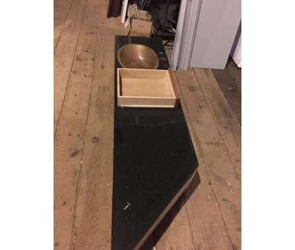 Black granite counter top with a copper sink and drawer