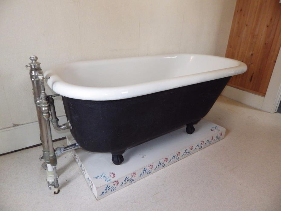 5 ft. cast iron L Wolff claw foot bathtub good condition with original faucets