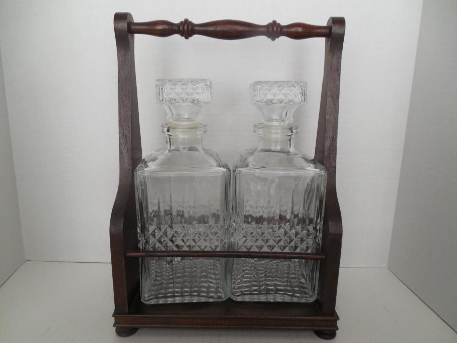Two pressed glass liquor decanters in a wooden rack