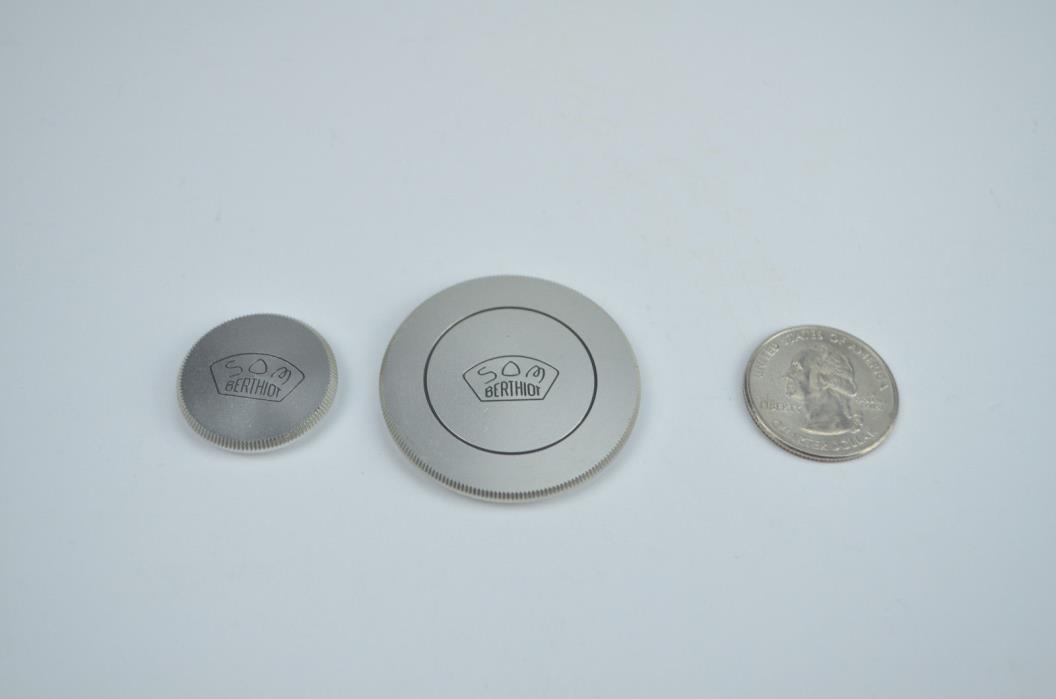 Two SOM Berthiot camera lens caps (different sizes)