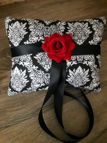 Black and white ring bearer pillow with a red rose, black ribbon.