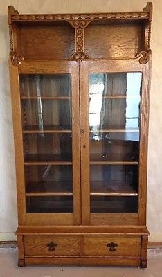 ANTIQUE LARGE OAK BOOKCASE WITH DOUBLE GLASS DOORS & CARVED ACCENTS -