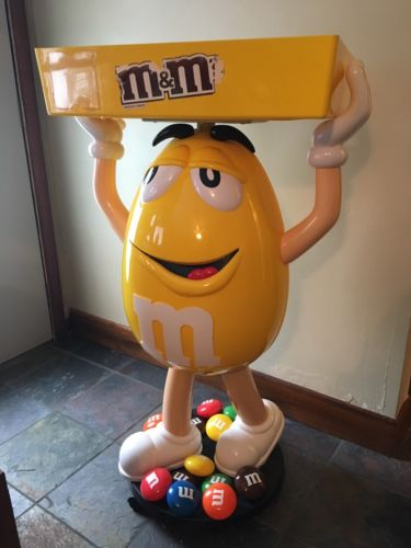 M&M YELLOW CHARACTER DISPLAY WITH STORAGE TRAY 46 INCHES TALL GOOD CONDITION