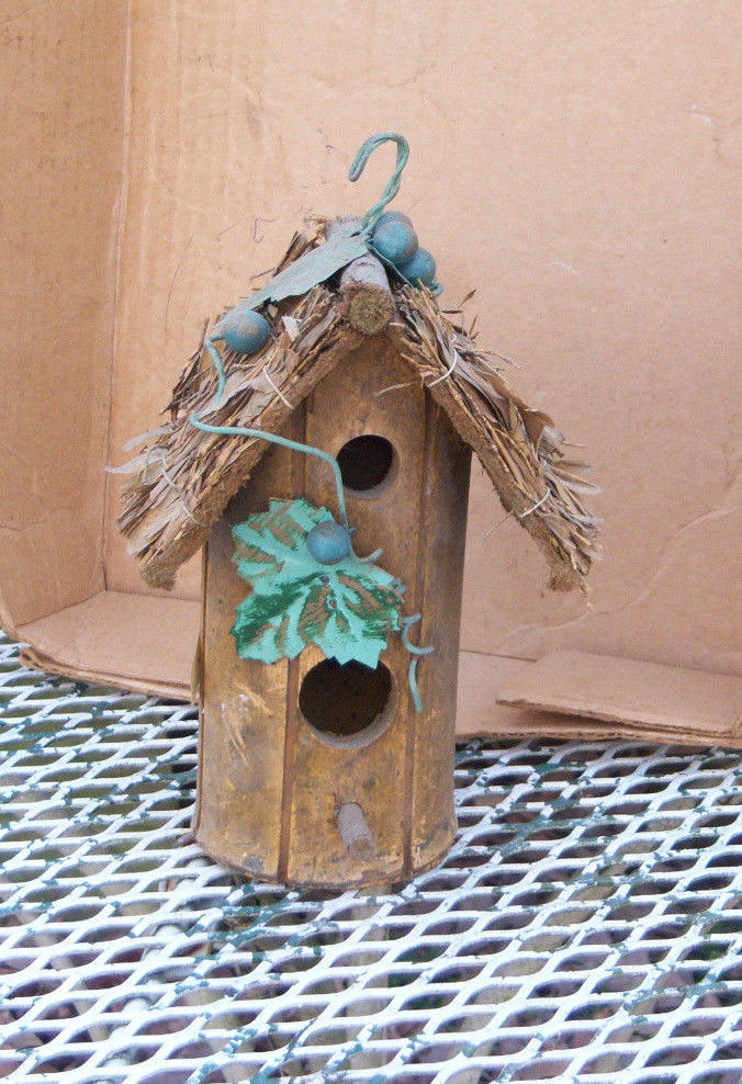 Wooden round log birdhouse with one opening and a perch